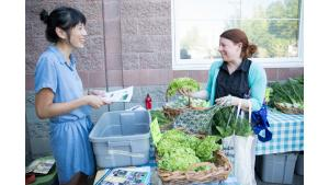 An OHSU employee chats with farm share participant Andie Amour.