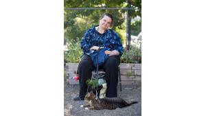 Farm share member Mary Casey takes a break in the shade with her cat Cooper.
