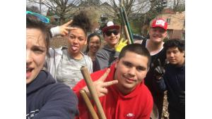 Diverse group of teens smiling as they work in a garden