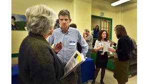 Health Officer Dr. Paul Lewis, center, and Deputy Health Officer, Dr. Jennifer Vines, second from right, talk to neighbors about high levels of heavy metals in recent air testing.