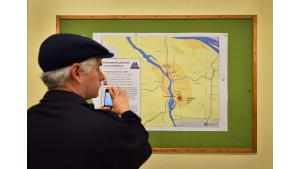 A community member snaps a photo of a map displaying estimated cadmium concentrations in Portland.