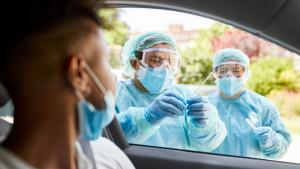 Man in a car getting tested, two health care workers in protective gear take sample.