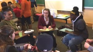 Four students sit in a circle talking