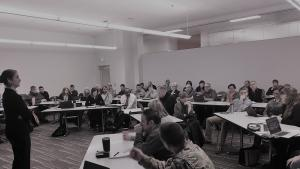 Room full of people sitting at desks.  Woman standing in front, wearing black, addressing the group