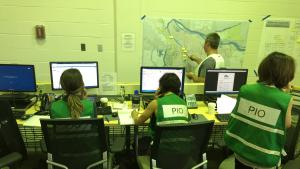 PIOs in green vests working on computers and on the phone
