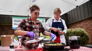 Rockwood Health Center's Jeff Holland and Elisa Sanchez get cooking during a recent demonstration in front of the outer Southeast county clinic.