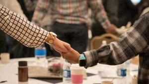 Photo of mother and son holding hands at the Black Men and Boys Healing Summit last Summer