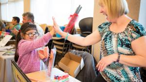Allison Saldana, age 8, gives a high five to Barbara Broderick, with Multnomah County's school oral health program