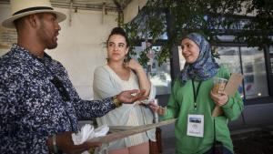 The MET's Rania Ayoub, right, talks to festival visitorsJose Zitlapopoca and Maria Garcia