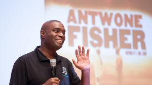 Antwone Fisher stands on stage to share his story with POIC + Rosemary Anderson High School and Multnomah County staff.