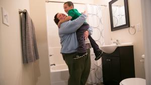 Andrea Bunch holds her son, Michael, 4, in their new bathroom. They moved into an apartment as part of the Home for the Holidays campaign.