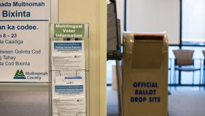 A display holds multilingual information about voting.  You can see inside the Voting Center Express and see voting booths and an official ballot drop box.