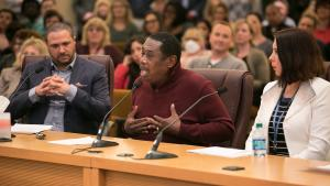 Clinical health specialist and Employees of Color ERG member Larry Turner (center) addresses the board as Chief Diversity and Equity Officer Ben Duncan (left) and Immigrants and Refugees ERG Chair Victoria Cross (right) look on.