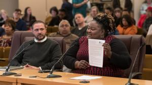 Chair Kafoury's Chief of Staff Kim Melton displays the draft Implementation plan as Chief Diversity and Equity Officer Ben Duncan looks on.