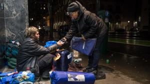 Perlia Bell, an outreach worker with JOIN, offers a tarp to Josh on a street in downtown Portland on Dec. 17, 2018.