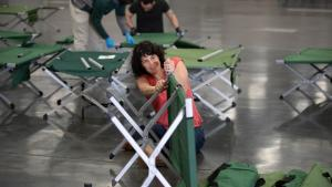 Commissioner Sharon Meieran joins in as County employees work to set up temporary shelter space at the Oregon Convention Center.