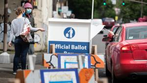Photo of a ballot drop site with voters dropping off their ballot.
