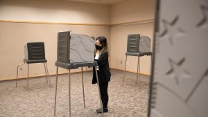 Voter wearing face covering votes in a voting booth at the Voting Center Express in Gresham