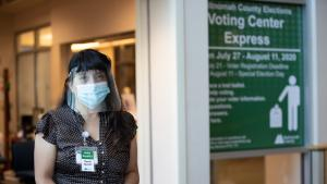 """Elections staff wearing a face shield, face mask, and gloves stands in front of the Voting Center Express in Gresham.  She is holding a clipboard and wears an """"I Speak Spanish / Hablo Español"""" badge"""