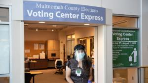 An elections worker waits to greet voters at the Voting Center Express in Gresham