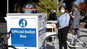 Voter returns a ballot to an Official Ballot Drop Site by bike