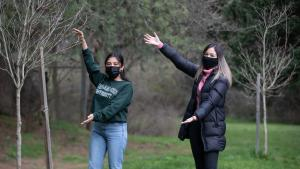 Two people smiling with masks next to a tree