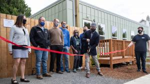 Partners in supporting the St. Johns Village watch Do Good Multnomah director Chris Aiosa cut a ceremonial ribbon on May 21, 2021.