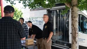 Mental Health Unit officers John McVay and Joe Wenhold, alongside College to County intern Zola Neal, set up a stand and lay out socks, bottles of water and box lunches