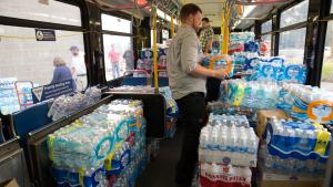 A bus filled with crates of bottled water