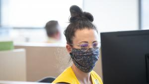 Multnomah County staff person with brown hair in a bun and glasses with mask on sits at a computer at the Emergency Operations Center