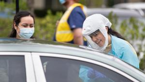 two people dressed in protective gear talk to someone in a car waiting to get tested