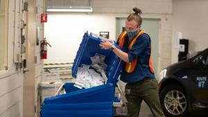 An election worker empties a ballot box of returned ballots in August 2020 at the elections office.