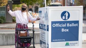 A voter returns their ballot to an Official Ballot Drop Site