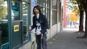 A voter on a bicycle returns their ballot to an Official Ballot Drop Site.