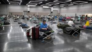 People spaced on cots inside the Oregon Convention Center