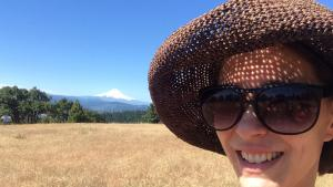 Woman with sunglasses and a hat, smiling in a field with Mt. Hood in the background