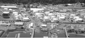 Picture of large tanks for storing petro-chemicals along the Willamette River with docs for loading and off loading petro chemicals in the fore ground.