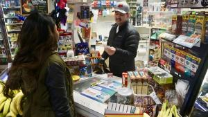 Frederico Villalobos at the Porvenir Mini Mark in East Portland models how vendors should check for ID when people purchase nicotine products.