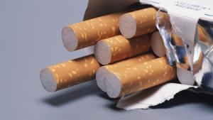 Pack of cigarettes on its side with 5 sticking out