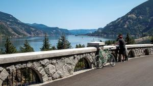 Photo of two people standing with bike on railing of Columbia River Highway with view of the gorge
