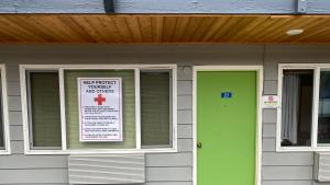 Picture of door and poster of safety guidance at the Banfield Value Inn shelter.