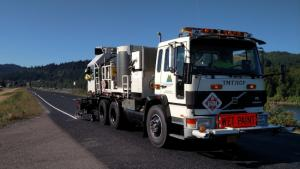"""A county paint truck lays down a white stripe on the side of an asphalt road, with forested hills in the background. A large orange sign on the front of the truck reads """"Wet Paint""""."""