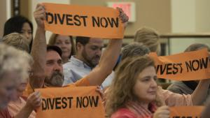 Activist show their support of the board's decision to divest in fossil fuel companies.