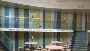 """Image of a common area at the Donald E. Long Juvenile Detention Facility. There is a quote painted on the balcony that says, """"'I read a book and one day my whole life was changed.' - Orhan Farmuk"""""""