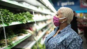 woman in the produce section of a grocery story with a cloth face covering
