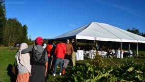 Wide shot of a tented seating area with a line of people waiting for the buffet.