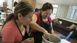 Karen Rivera stirs a pot of soup while her neighbor Micaelina Lopez looks on