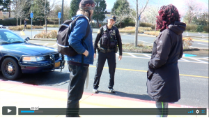 Two youth face a police officer on the street