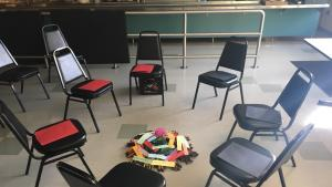 A circle of chairs surround a centerpiece with flowers and words of agreement