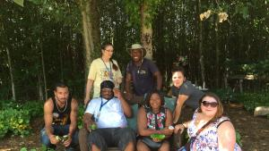 picture of students and instructors visiting the CROPS farm, and relaxing a bit in the shade. Farmer Jerry Hunter also posses in the picture.